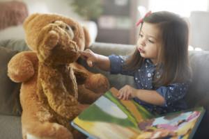 little-girl-reading-to-bear